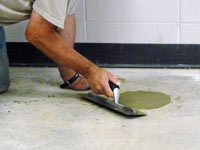 Repairing the cored holes in the concrete slab floor with fresh concrete and cleaning up the Camp Lejeune home.