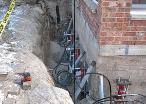 Foundation push piers installed around a house with a foundation settlement issues in Hubert