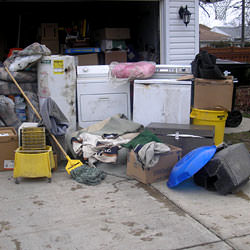 Soaked, wet personal items sitting in a driveway, including a washer and dryer in Sanford.