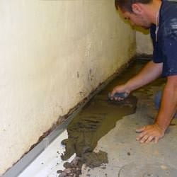 A basement waterproofer installing a perimeter drain system in Laurinburg