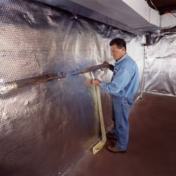 Installation of a radiant heat and vapor barrier on a basement wall in Saint Pauls